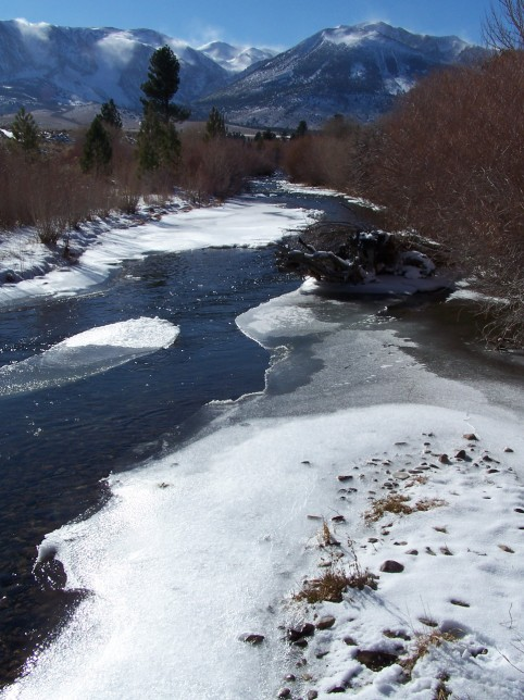 Snow banners blow off the peaks high above icy Rush Creek. Photo by Greg Reis.