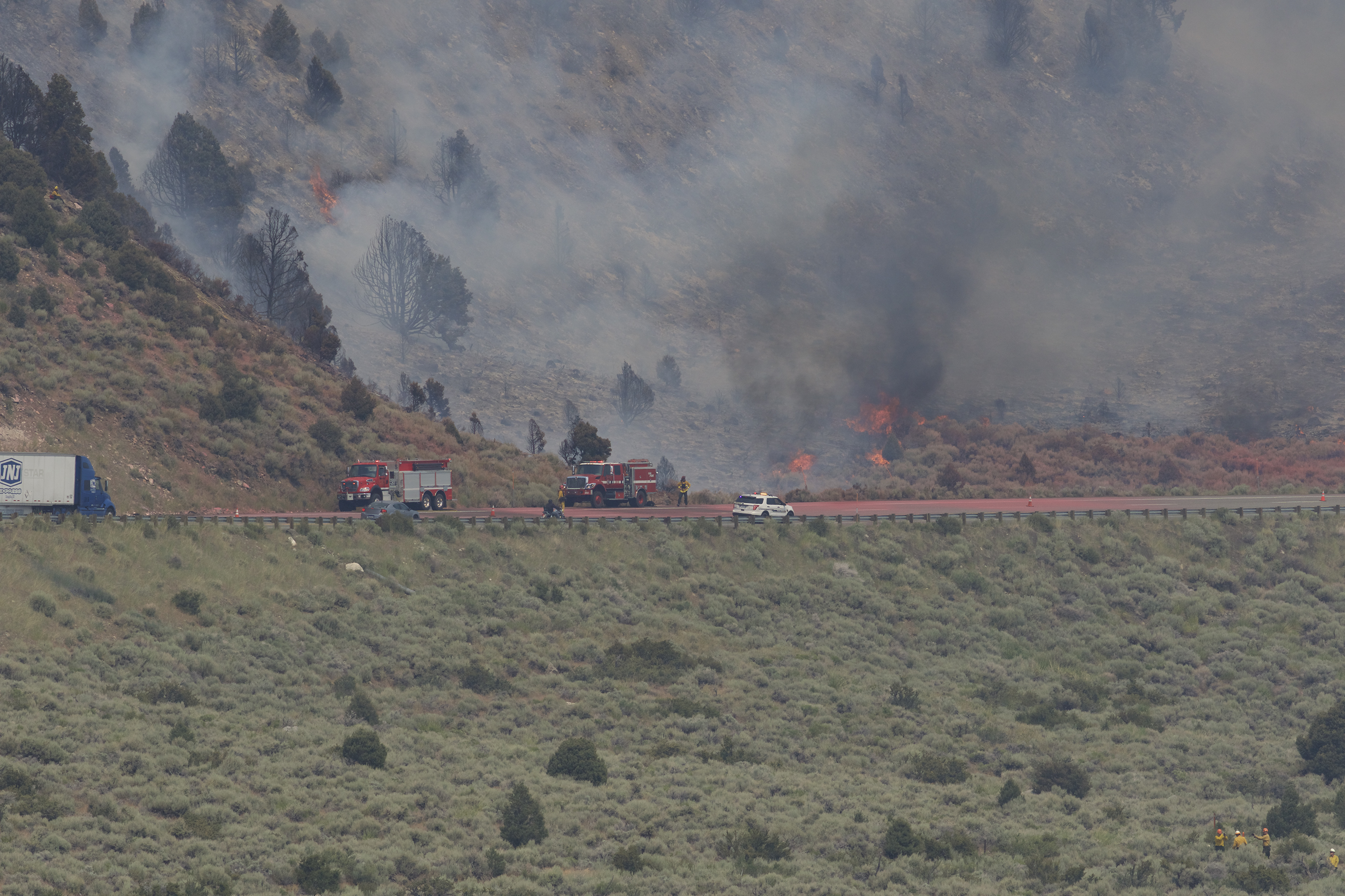 Fire personnel on Highway 395 and monitoring from below. Red coloration on the highway is fire retardant. Photo by Santiago M. Escruceria.