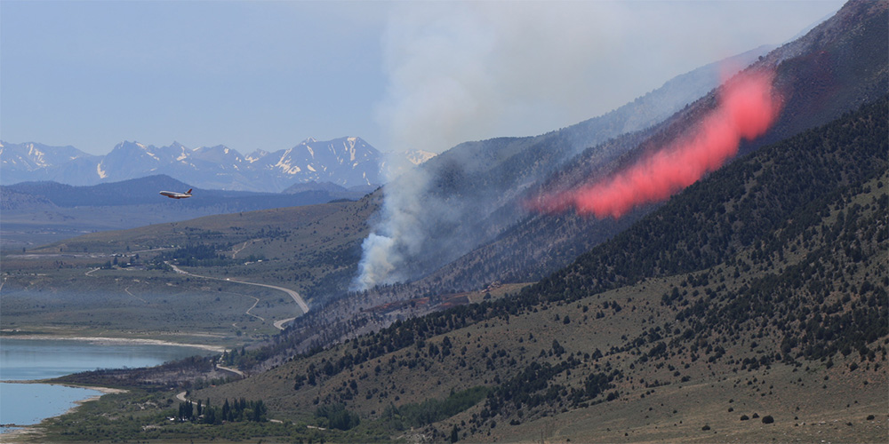 A DC-10 bomber drops fire retardant along the north flank of the Marina Fire on Saturday, June 25. Photo by Bartshe Miller.