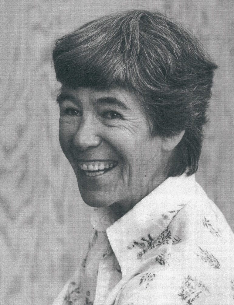 A black and white close up of a woman with short dark hair smiling and laughing at the camera.