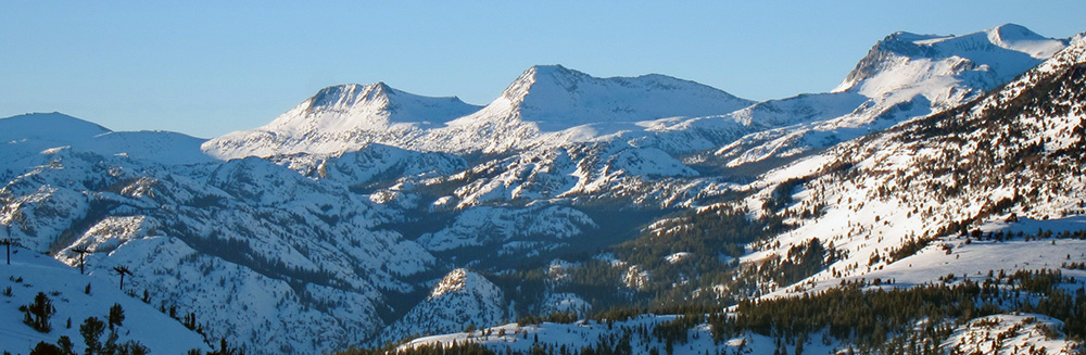 A view across an open snow-covered mountain valley spotted with pine trees to three alpine peaks above the tree line with rocky crags and the bright light and blue shadows of a sunset under a bright blue sky, with the middle peak being Mount Andrea Lawrence.