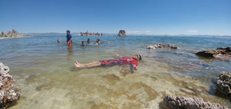A boy wearing goggles and smiling lays in Mono Lake near the shore, floating on his back. Clear blue skies and clear greenish blue water stretch out above, and more people are swimming.