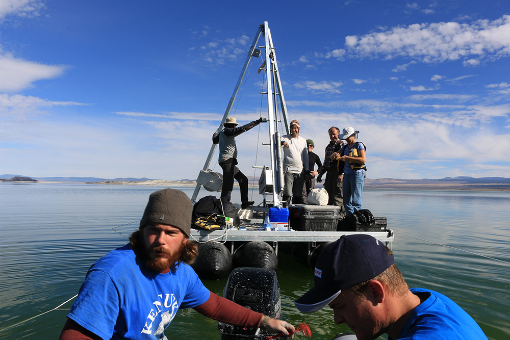 Seven researchers out on Mono Lake on a pontoon platform with tall metal hoisting structure and lots of research equipment on it, being pulled by a smaller motor boat.
