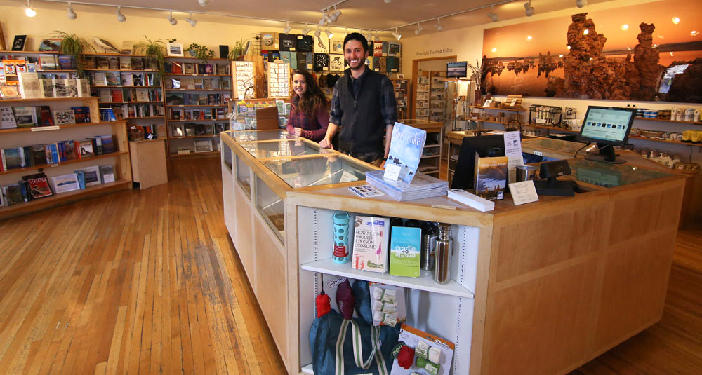 Two smiling people stand at the front counter inside the warm and welcoming Mono Lake Committe Information Center & Bookstore.