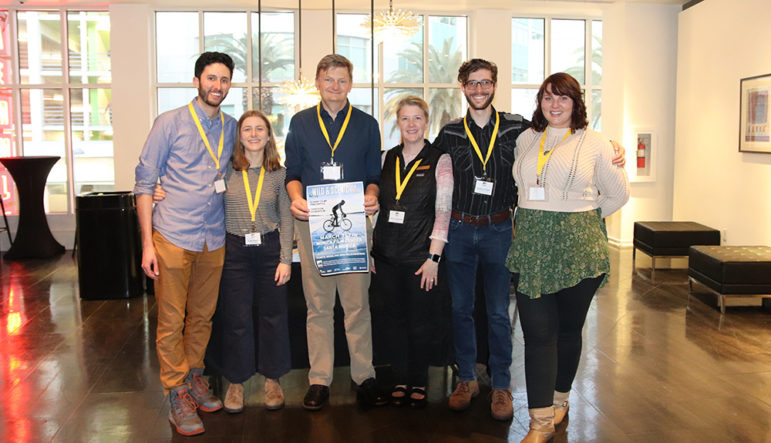 Six staff members of the Mono Lake Committee stand together indoors, smiling. Geoff McQuilkin holds a poster for the Wild and Scenic Film Festival.