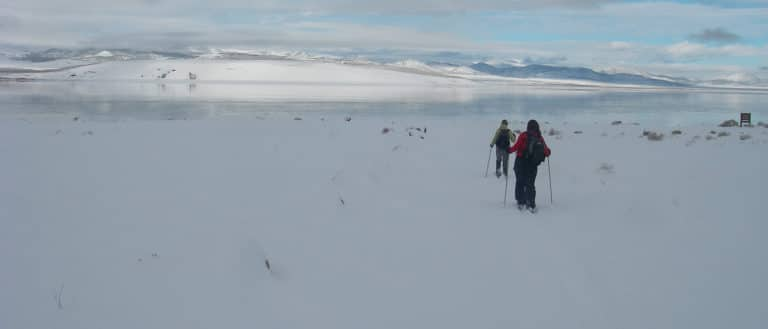 Two figures with ski poles are in motion in a snow field. Ahead of them, Mono lake is highly reflective of the white mountains and blue gray clouds.
