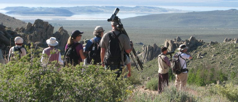 A group of eight people with scopes look in different directions into hilly sagebrush scattered with jutting gray rocks.