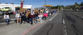 """A large group of protestors walk down Mattly Ave with signs reading """"Black Lives Matter"""" and """"Enough is Enough"""". The Shell gas station is behind the group and there is a blue sky."""