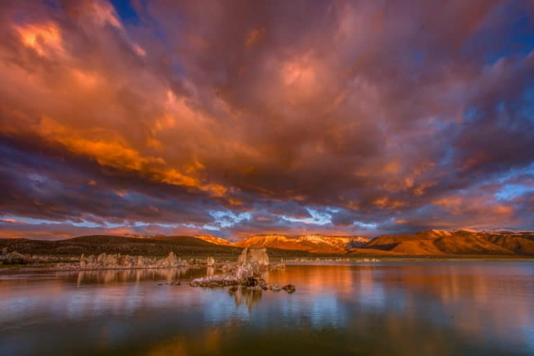 Stunning sunrise view at Mono Lake looking across the water, west to the Sierra Nevada which has golden light and dramatic stormclouds above a colorful reflection and tufa towers in the foreground.