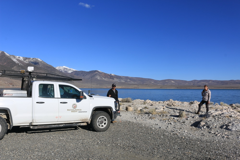 "Two people stand on the rocky gray beach in front of a white truck which says ""water and power"". The sky is blue and cloudless and the water is bright blue."