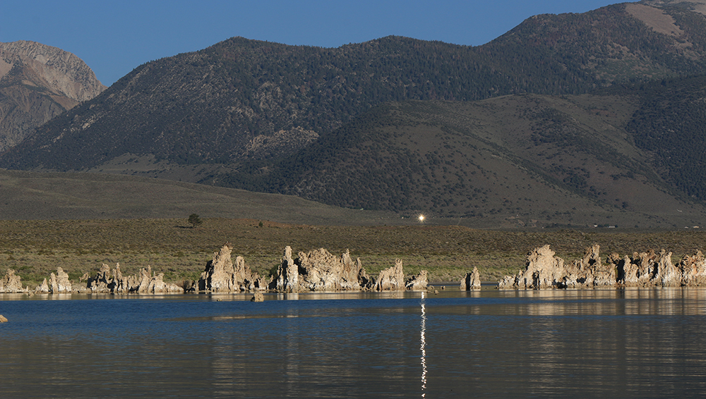 A bright light from the green hills across Mono Lake shines and reflects a line of yellow light on the blue rippling water.