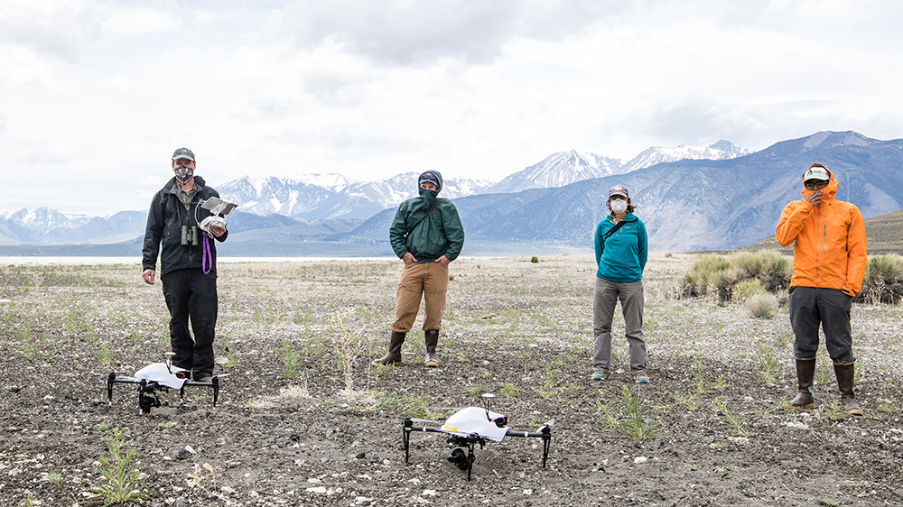Four people wearing rain coats, boots, hats and masks, stand apart behind two drones which are sitting on a rocky ground. The snow capped Sierra Nevada mountains are behind them.