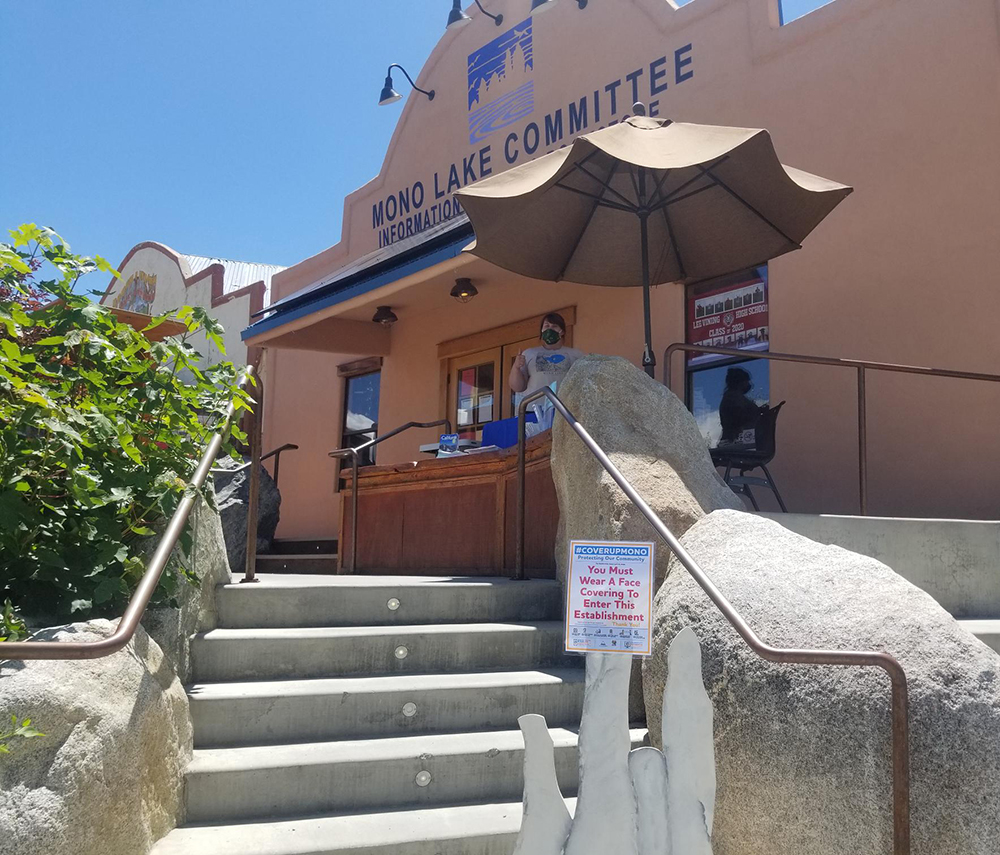 A woman in a face mask stands at a desk outside of the Mono Lake Committee building at the top of the stairs. There is an umbrella open to block the bright sun, and a small sign at the bottom of the stairs establishing Covid protocol.