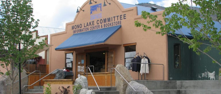 Mono Lake Committee Information Center & Bookstore storefront with a blue awning, trees, stairs, large landscaping rocks, and doors open to the public.