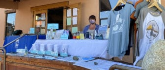 Woman in a face mask at a table set outside the Mono Lake Committee Information Center & Bookstore with information for visitors.