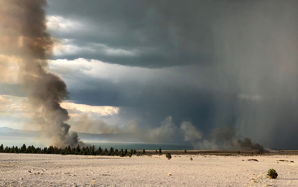 Sand and evergreens with a glimpse of dark blue water are shown partially covered by two dark gray smoke plumes, as well as a striping of smoke in the right side of the sky.