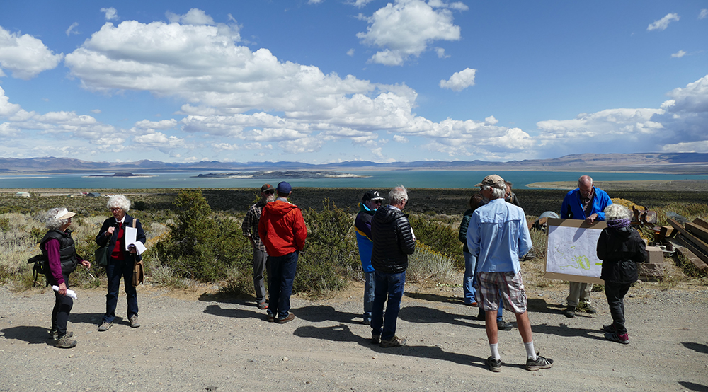 A group of several people survey the area on a gravel patch, looking out at the vast turquoise waters of Mono Lake. Some hold papers and point to maps. The sky is blue with clouds, and mountains stretch beyond the lake.