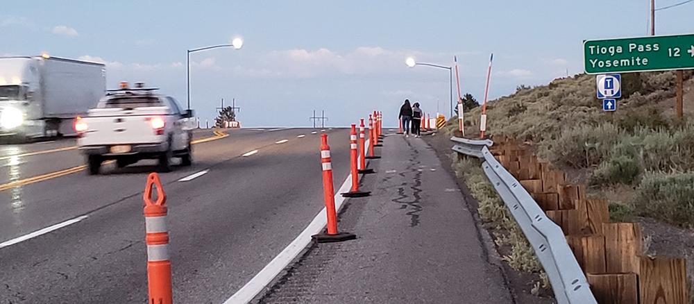 A white truck zooms past two pedestrians walking along the shoulder of the highway which is separated by orange cones.