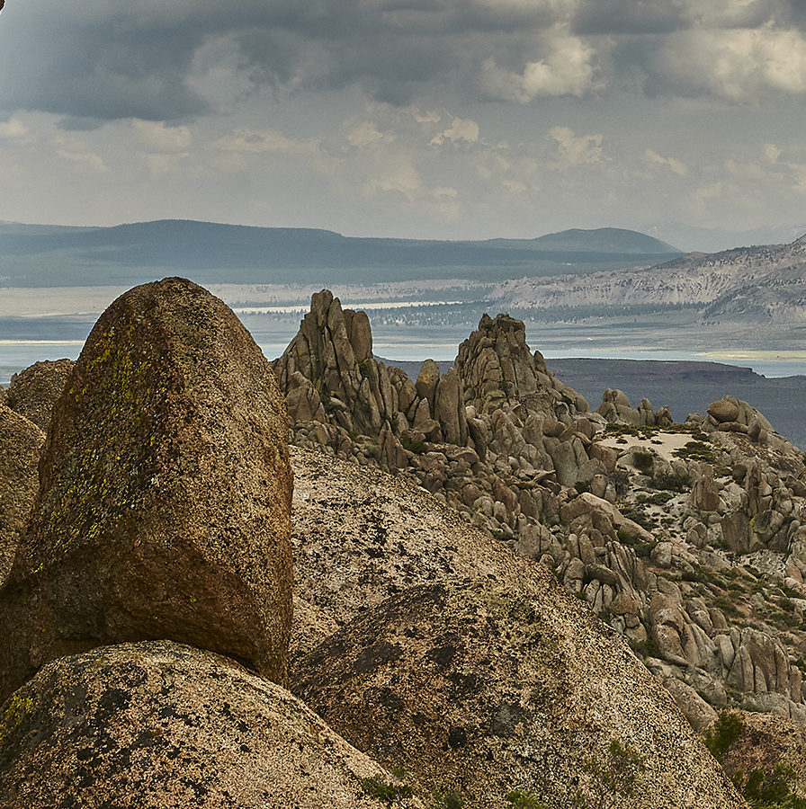 Unusually rounded granite rock piles and outcroppings in the foreground of a view out to Mono Lake with the Mono Crater plug domes in the distance.