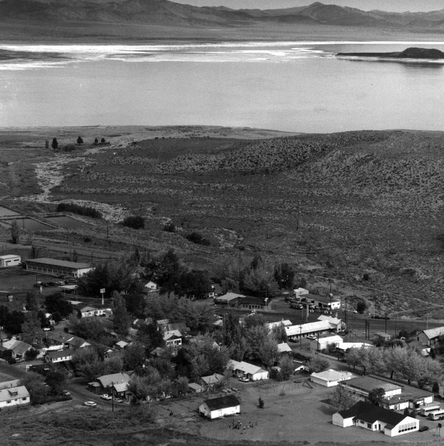 A black and white photo of the small town of Lee Vining, taken from a hill above, showing about 30 homes and shops with Mono Lake and black Negit Island and white Paoha Island, and the full moon rising in the distance.