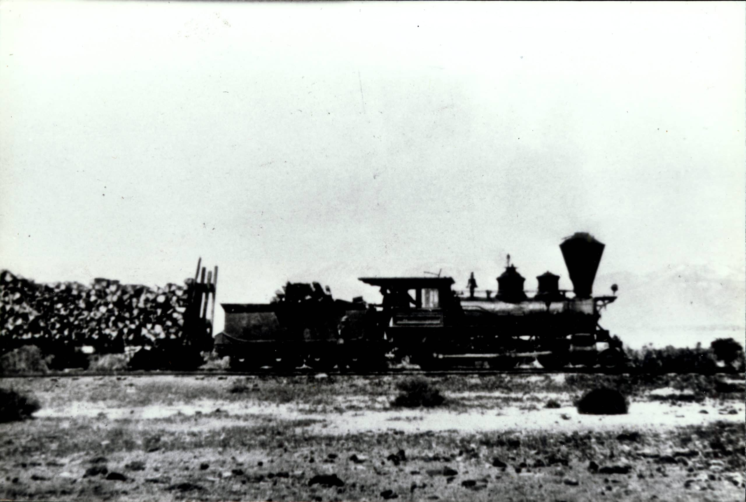 Black and white image of a locomotive carrying a load of logs.