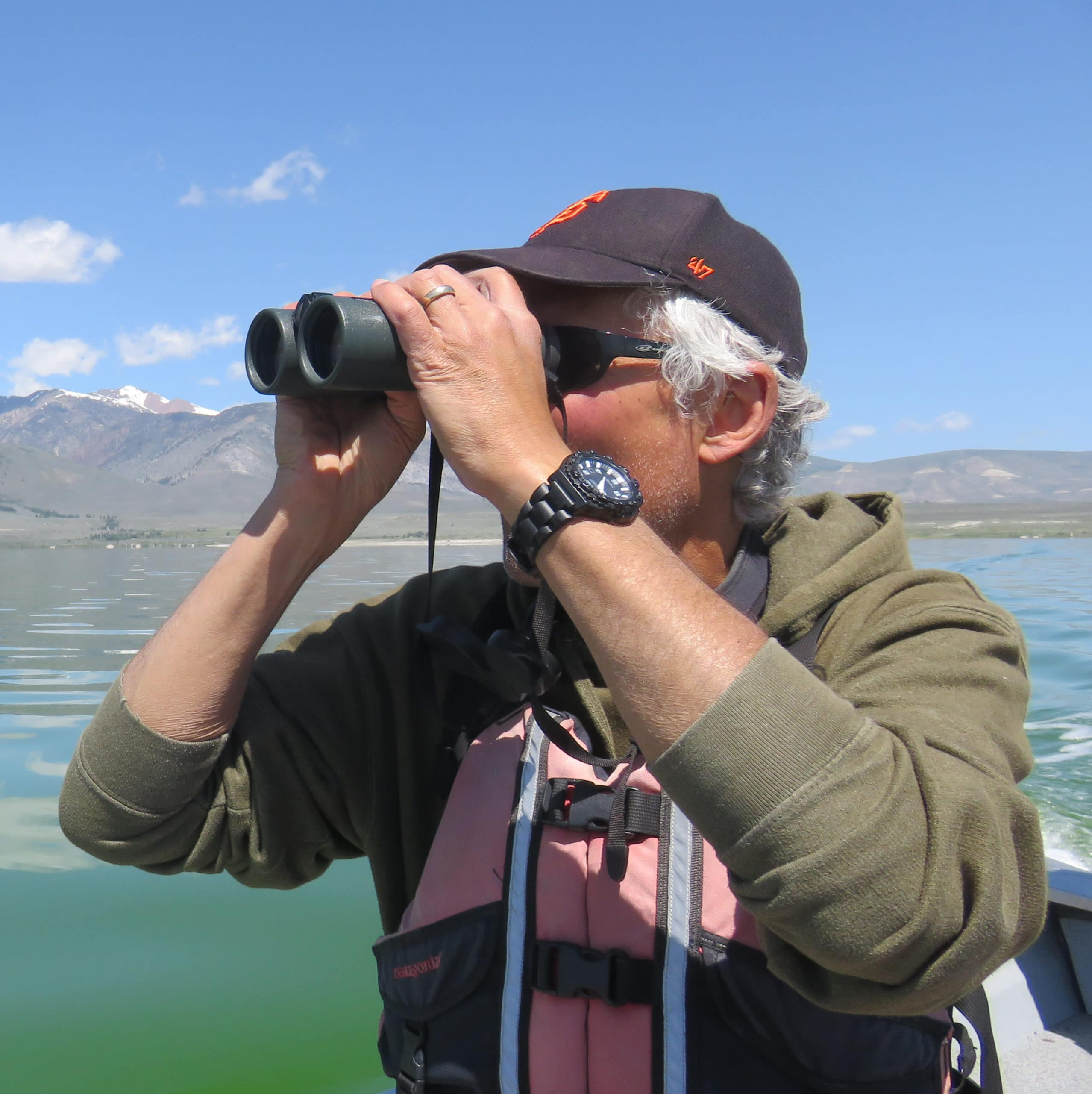 Researcher holds a pair of binoculars up to his eyes while wearing a life jacket and sitting on a boat with Mono Lake and mountains in the background.
