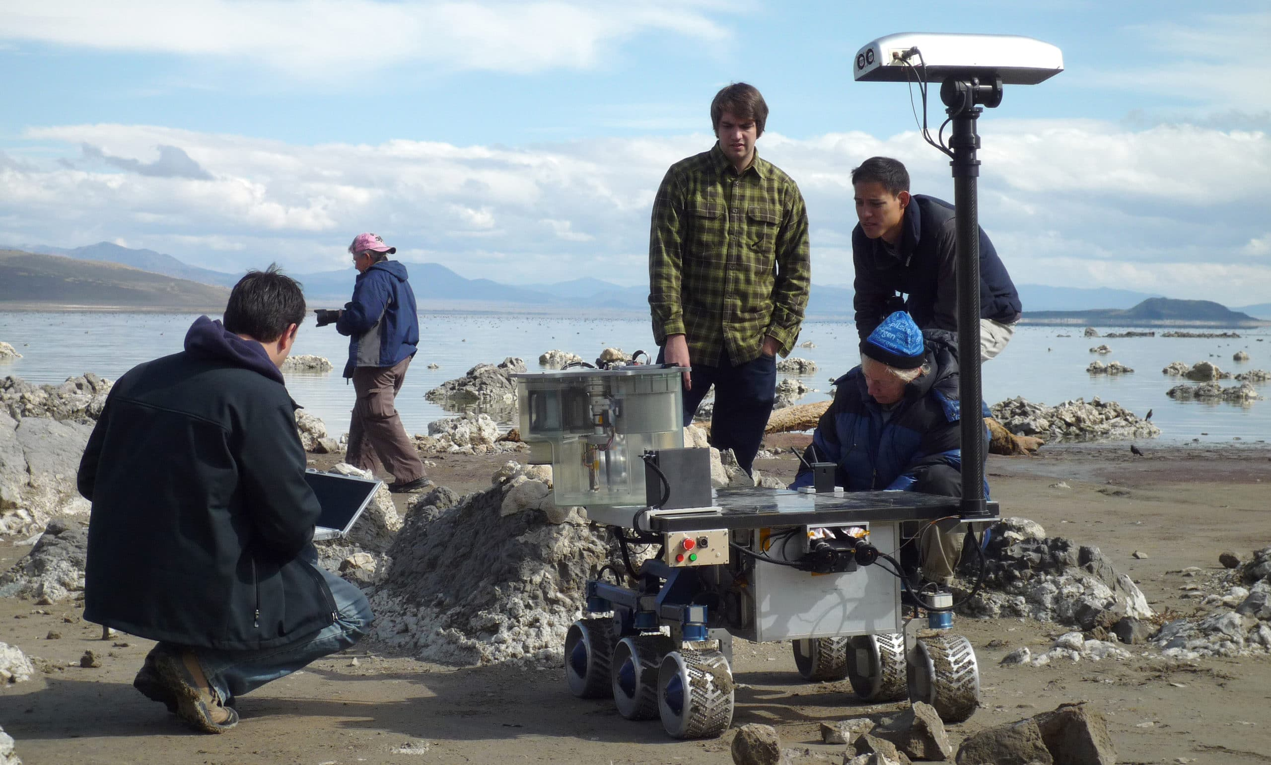 Four people on the shore of Mono Lake watching a prototype of the Mars Rover, a rolling platform with six wheels and various instrumentation, as it approaches a tufa mound.