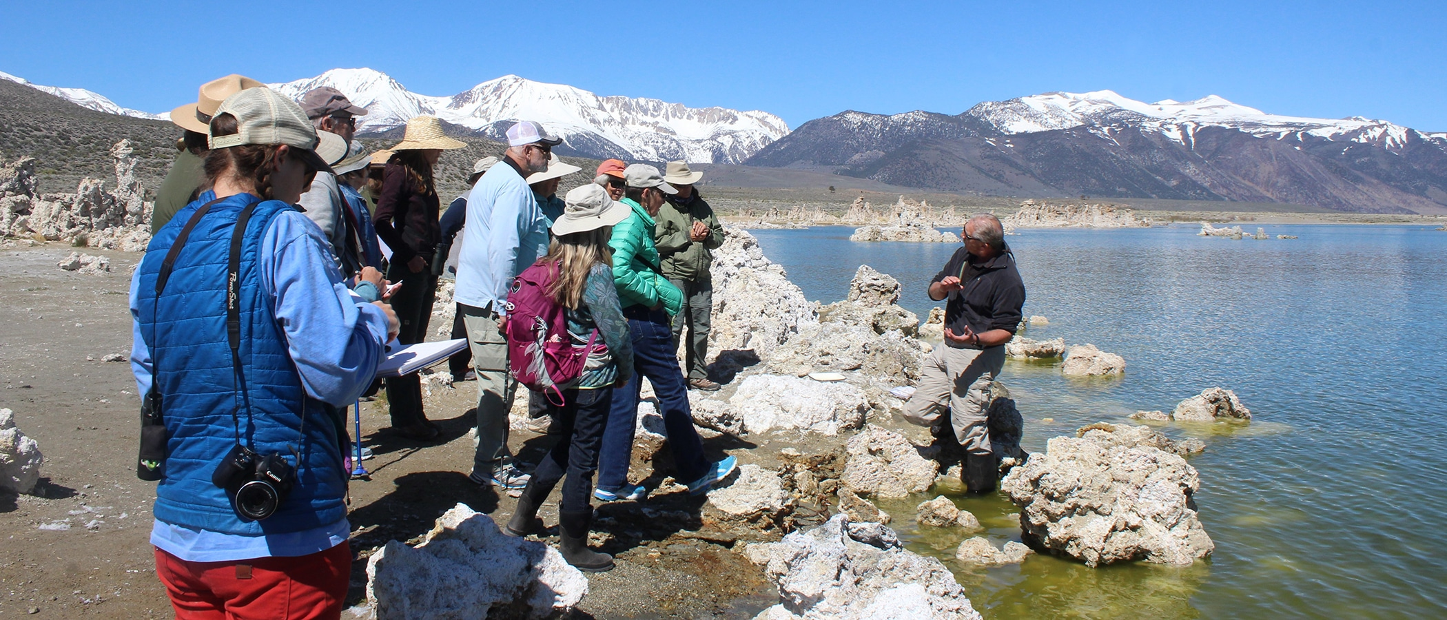 About 15 people standing on the Mono Lake shoreline listening to a person standing in Mono Lake leading a tour on a beautiful sunny day with the snowy Sierra Nevada in the background.