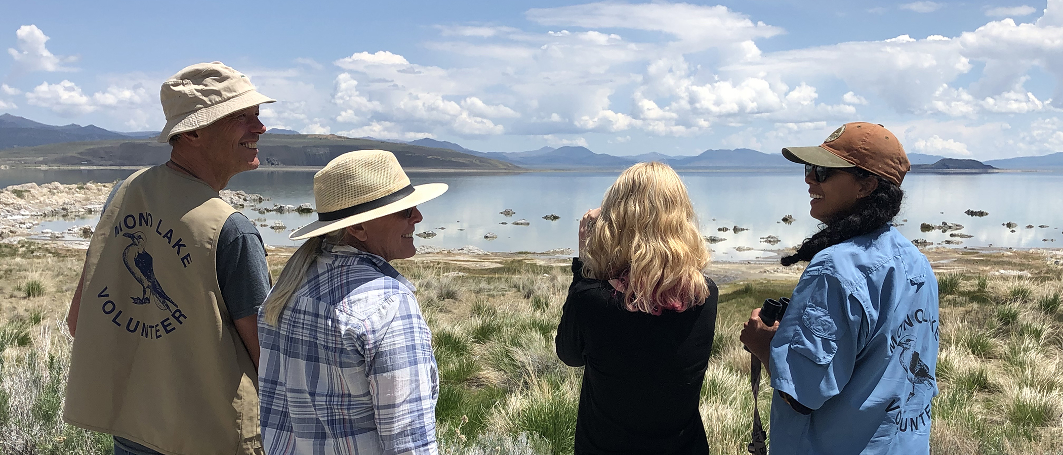 Four people overlooking Mono Lake on a bright sunny day smile at eachother while one looks through binoculars and tow of them have official Mono Lake Volunteer shirts and vests.