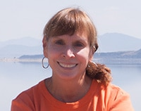 Woman smiling looking straight into the camera with Mono Lake in the background.