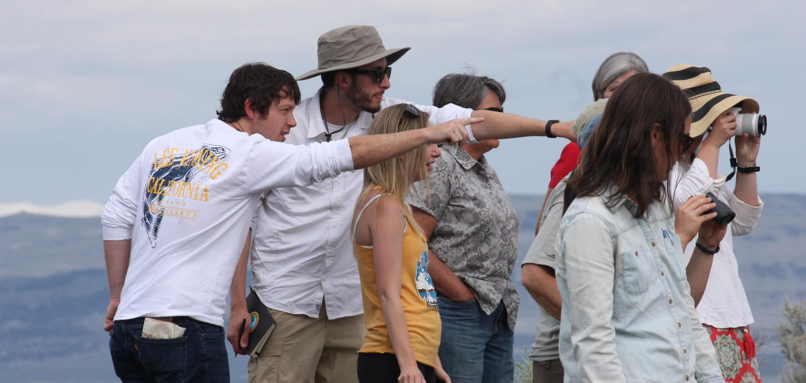 Nine people are looking at something interesting off in the distance, that we cannot see, and two people are pointing it out to one of the people, one is looking with binoculars, and one person is taking a photograph.