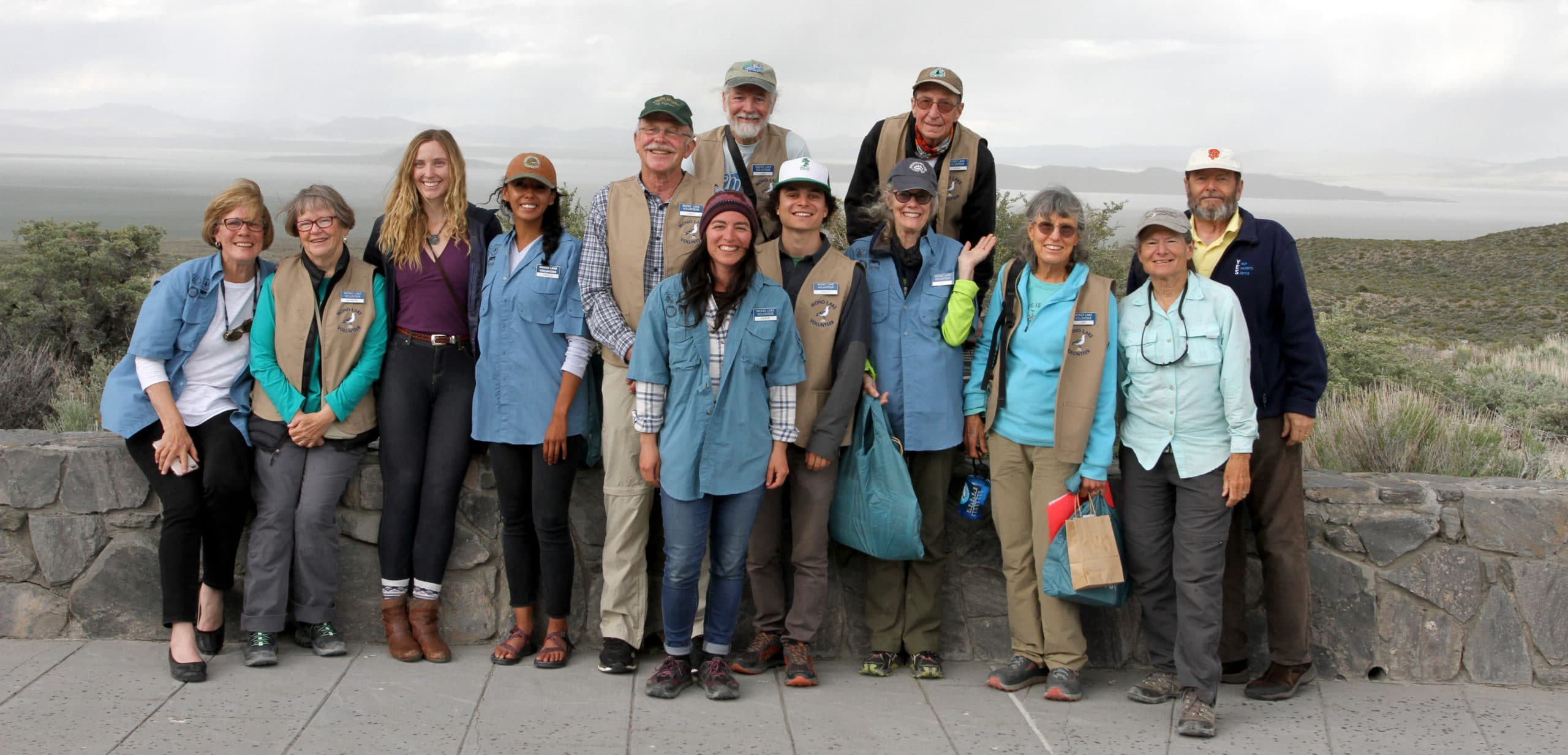 Thirteen people are standing together for a group photo smiling and looking very cheerful as they've just graduated to become official Mono Lake Volunteers.