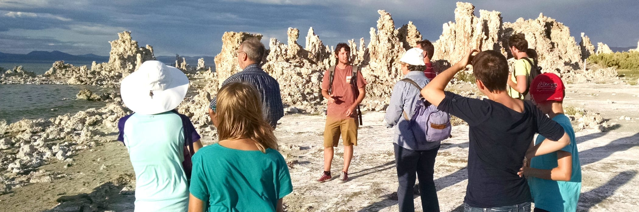 Tour guide talking to nine people at the shore of Mono Lake with tufa towers in the background, dramatic storm clouds, and the shoreline nearby.