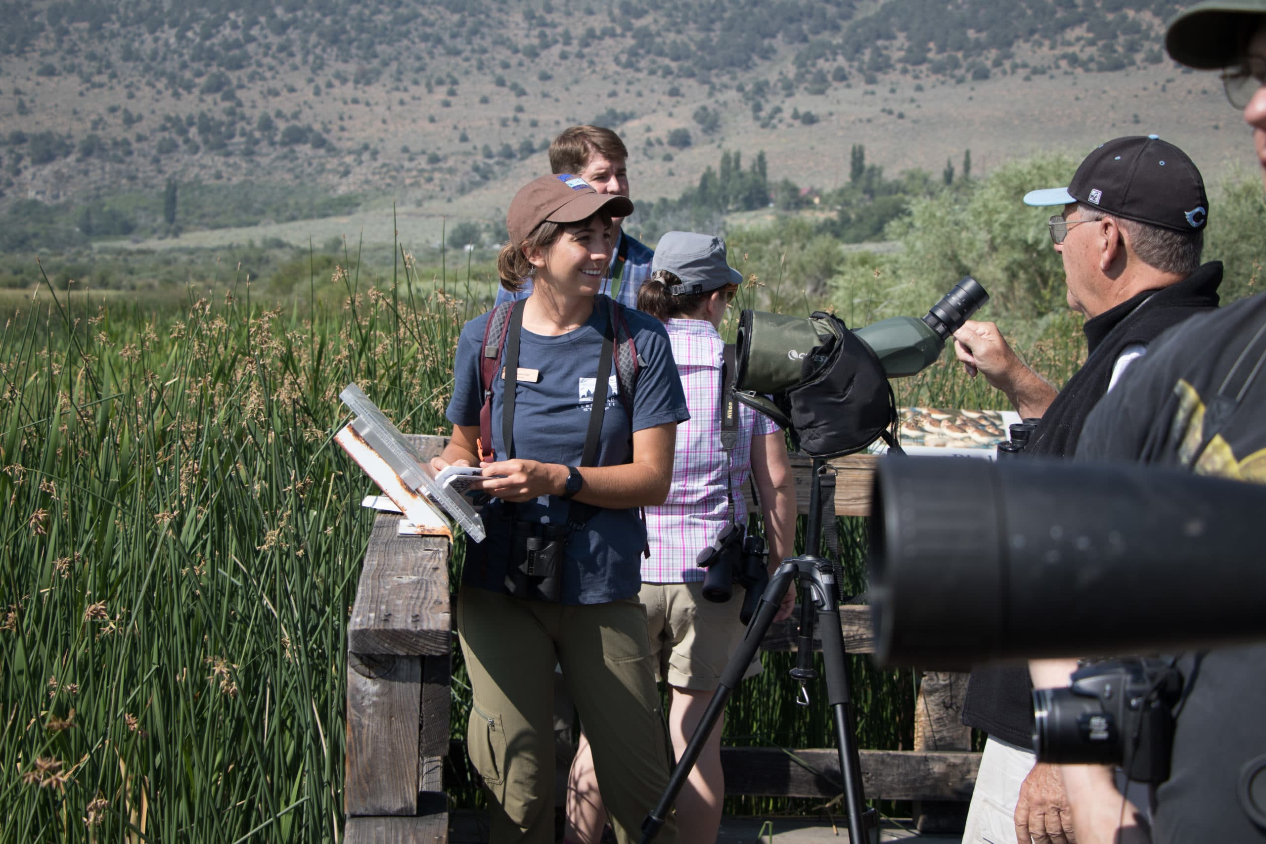 Five people with binoculars and spotting scopes are gathered on a wooden platform among marsh reeds happily doing some bird watching on a bright sunny day.