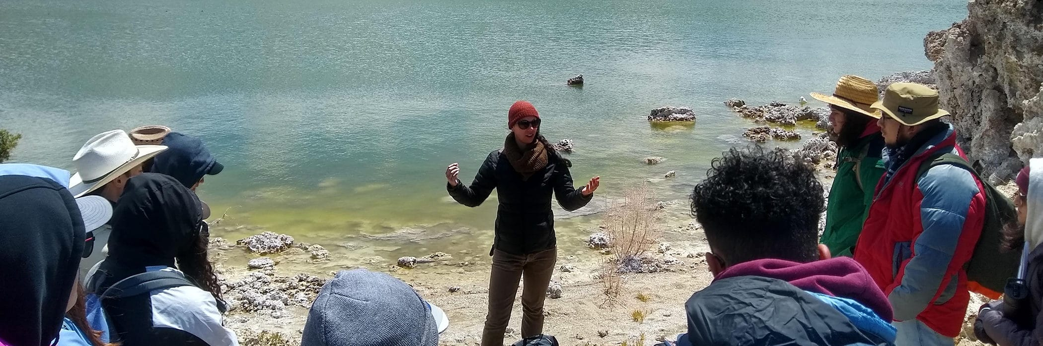 Eleven people gather around a woman giving a tour at the shore of Mono Lake with the lake water in the background and the tour participants bundled up in warm outdoor gear.