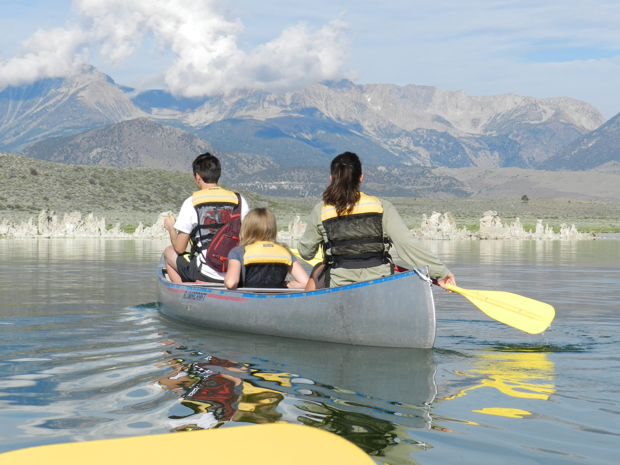 Three people sitting in a canoe paddling on Mono Lake in the bright sun moving over glassy water towards a grove of tufa towers with the tall Sierra Nevada in the distance.