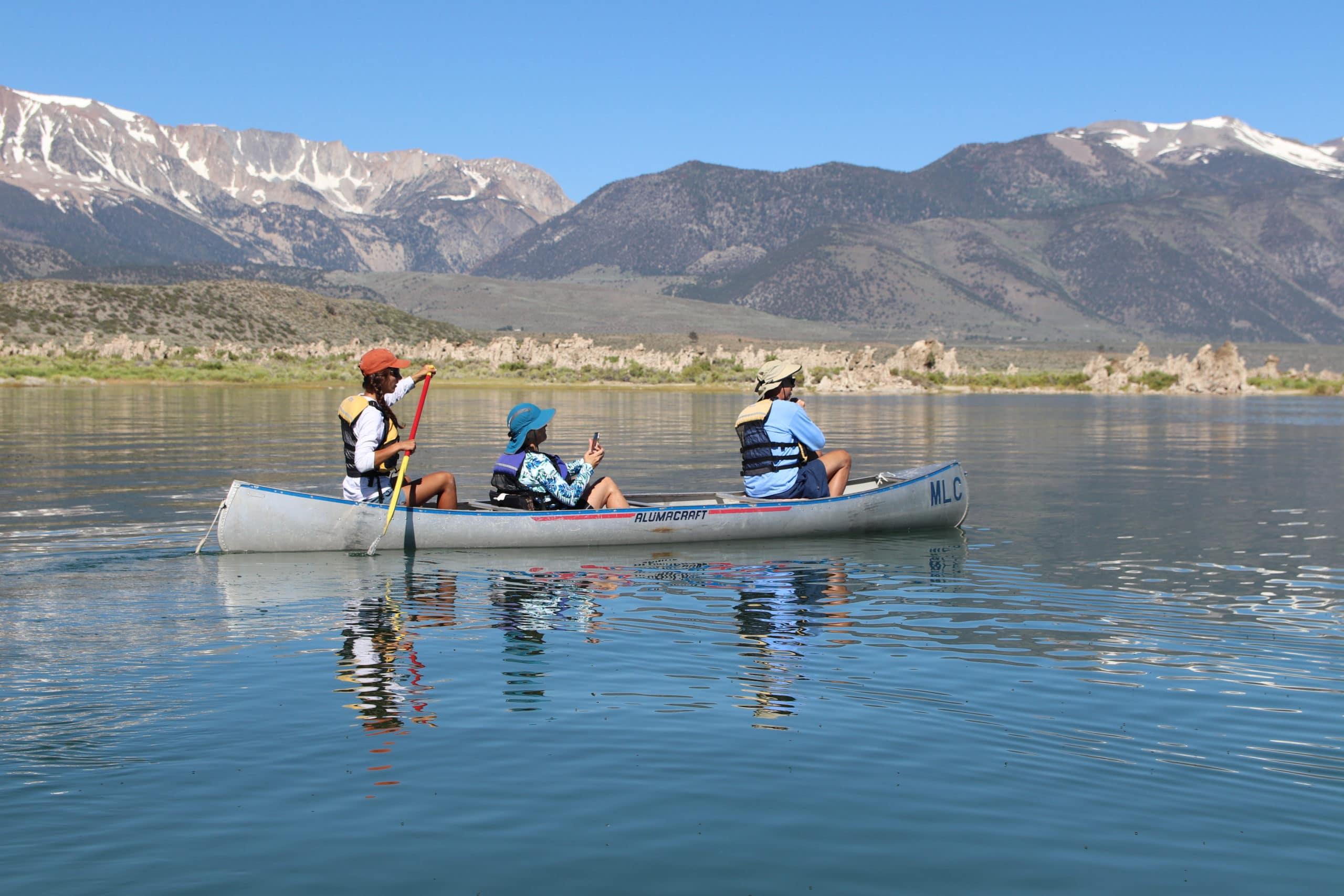 Three people canoeing on Mono Lake on glassy water with tufa towers and tall mountains with snow on them in the distance.