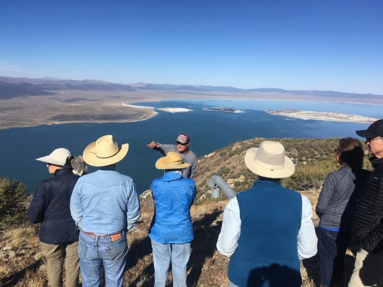 Six people gather around a guide who is using his hands to describe something, and the group is standing on a high precipice overlooking Mono Lake stretched out in a large expanse of blue with a clear view of the islands in the lake and the desert all around.