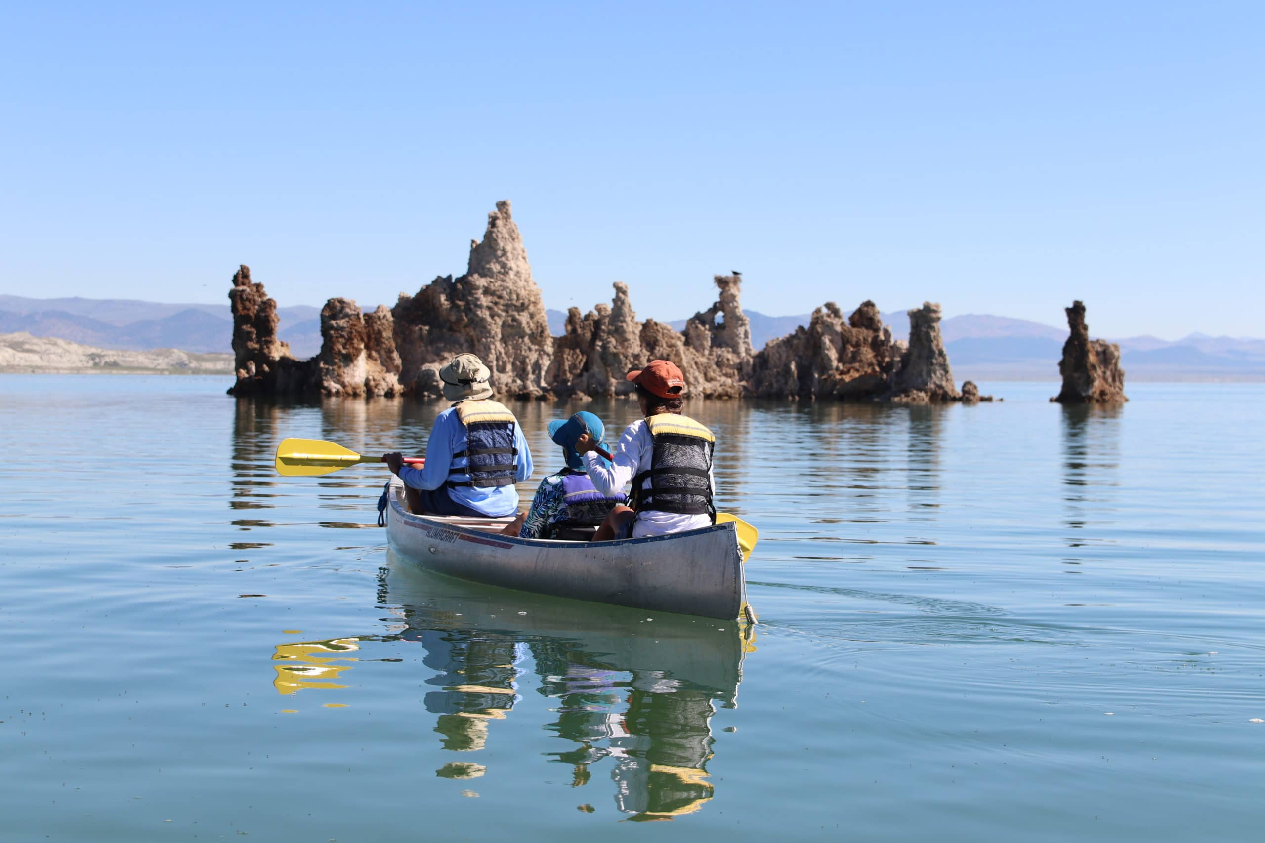 Three people canoeing on a bright sunny day on glassy Mono Lake towards an island of tufa towers with a large stick nest atop one of the towers and a fish-eating hawk, Osprey, perched on top.
