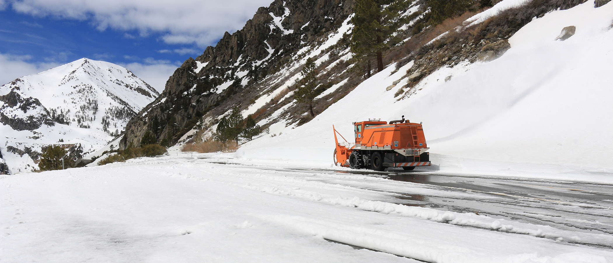 Orange Caltrans show removal vehicle next to a tall bank of snow with snow in the foreground.
