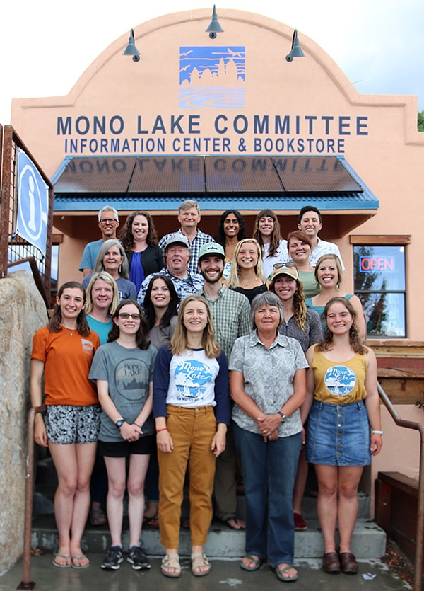 Twenty people stand together for a group photo on the steps on the Mono Lake Committee Information Center & Bookstore.