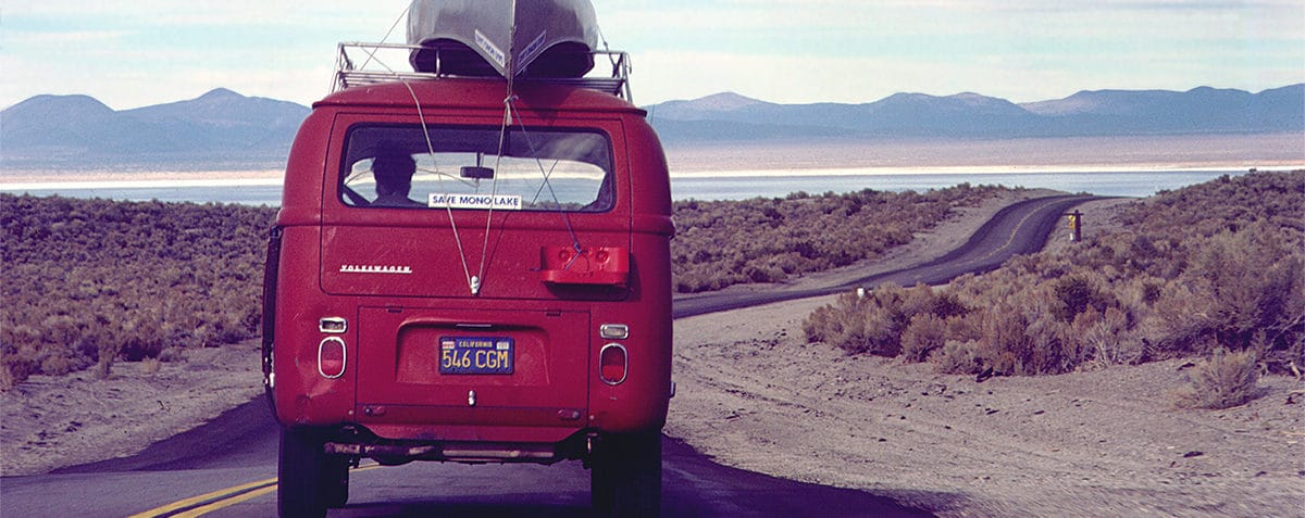 "A bright red Volkswagen van with a metal canoe strapped on top and a ""Save Mono Lake"" bumper sticker drives down a two-lane highway towards Mono Lake in the distance."