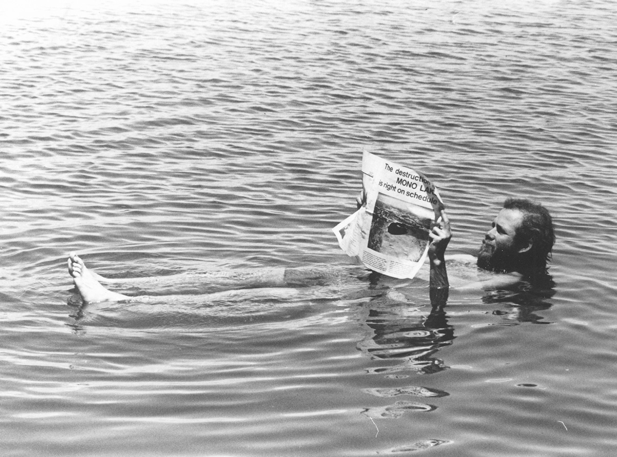 "A bearded man, David Gaines, co-founder of the Mono Lake Committee floats on his back in Mono Lake while holding a newspaper that reads"" The destruction of Mono Lake is right on schedule""--a fun publicity stunt."