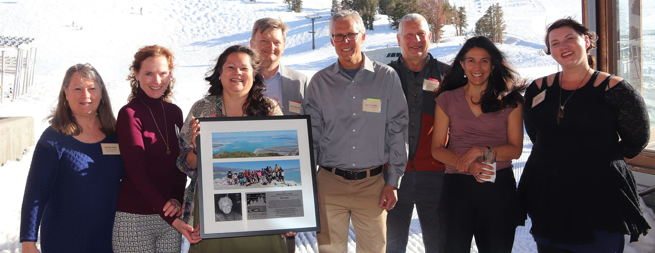 A group of 8 smiling people pose, one is holding a framed award with photos on it.