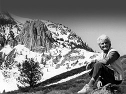 Black and white image of Andrea Mead Lawrence sitting on a rock with the craggy rocks and snow of the Sierra Nevada behind her.