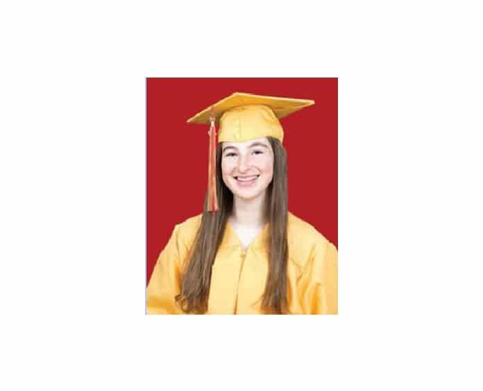 Graduation photo of a young woman in a yellow cap and gown against a red background, smiling.