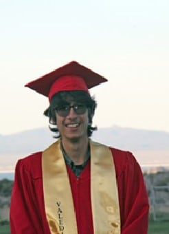 """A young man in a red graduation cap and gown and a yellow """"Valedictorian"""" scarf."""