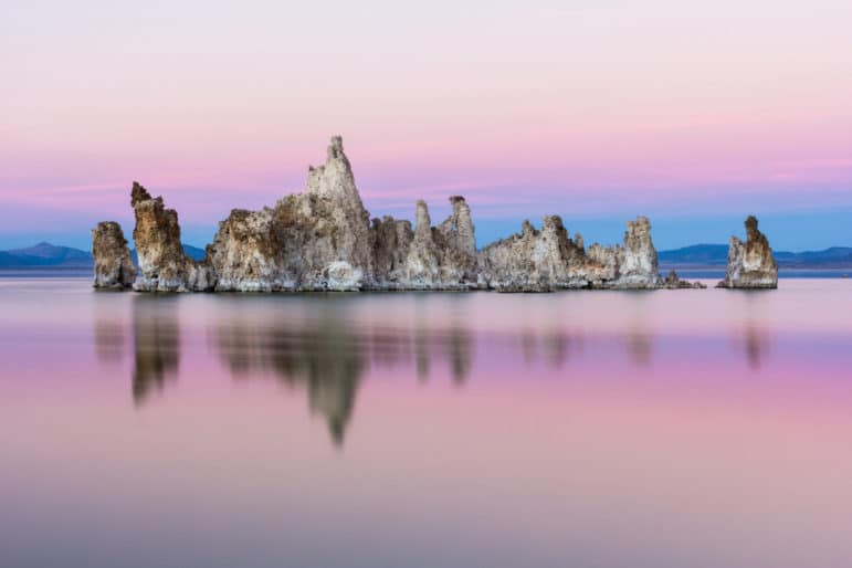 An island of tufa towers emerges from Mono Lake in a pink and blue soft hue sunset.