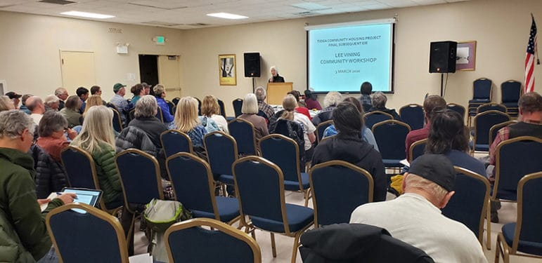 """Fifty or so people sit in a community center looking up at a person giving a presentation into a microphone at a lecturn in front of a screen that reads """"Tioga Community Housing Project Final Subsequent EIR, Lee Vining Community Worksshop""""."""