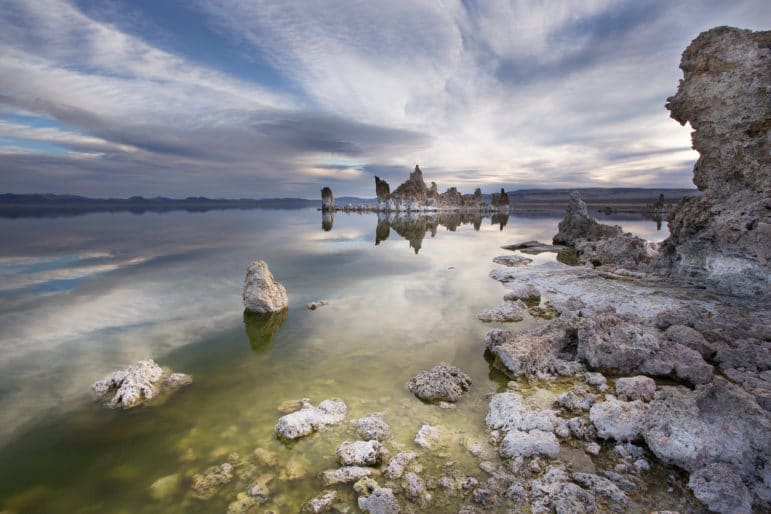 Dramatic scenic view of the shoreline of Mono Lake with a tufa tower and tufa rocks submerged in a green lake and large high clouds racing across the sky above an island of tufa towers perfectly reflected in Mono Lake.